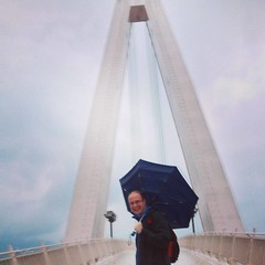 Dan with his umbrella inside out in the middle of the bridge.