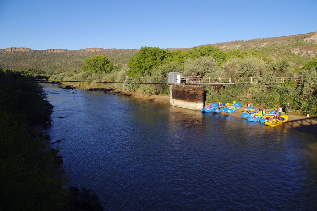 Rafts full of people and equipment on the banks of the Rio Grande near Otowi Bridge