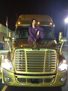 Katy Perry sitting on top of her Gold Prism Tour truck