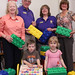 Judy Hagerman (Vice-Chair, Clarington Public Library Board), Ron Robinson (President, Kendal Lions), Karen Christopher (past President, Kendal Lions), and Janet Vanderveen (Branch Coordinator, Clarington Public Library) with two children from the Ontario Early Years program enjoying the educational toys generously donated by the Kendal Lions to the Orono Branch of the Clarington Public Library as part of the Lions Club 'Reading Action Program' (RAP).