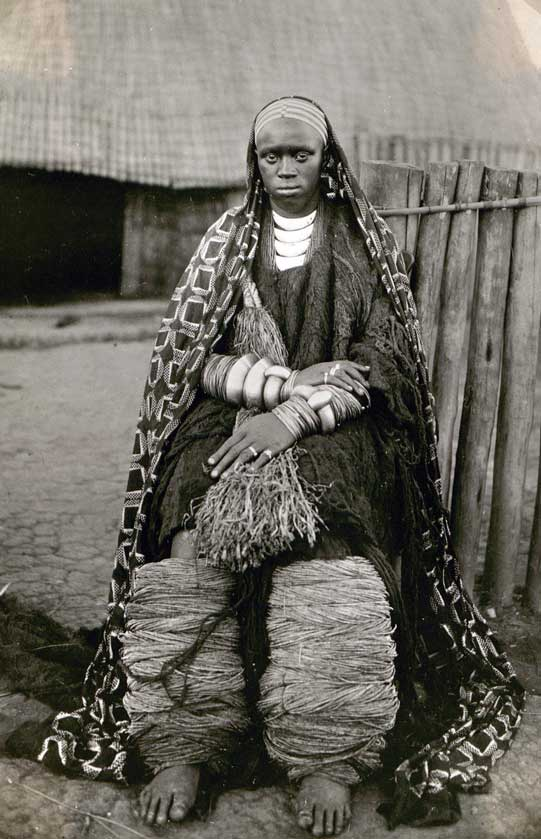 Well-of native woman sitting in front of a cottage, 1928.