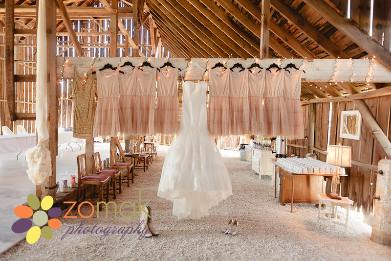 Wedding gown and dresses hanging from the rafters in a barn