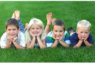 Four kids lying on the grass