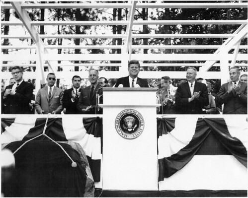 President Kennedy gets approval from audience and dignitaries at Grey Towers dedication ceremonies of Pinchot Institute for Conservation Studies. Note: Others on stage --  Secretary of Agriculture Orville Freeman, Chief of the Forest Service, Edward P. Cliff,  Pres of the Conservation Foundation Samuel Ordway, and  Governor of PA, William Scranton. Credit: US Forest Service, Grey Towers NHS