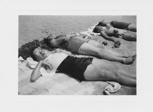 Women sleeping on the beach with old goggles