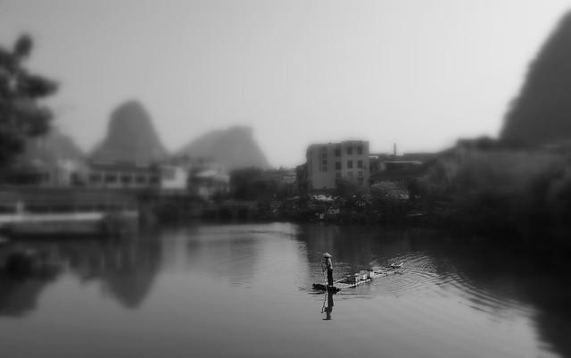 Man on a bamboo raft in Yangshuo, Guangxi, China.