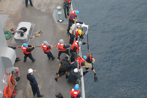 Crewmembers aboard the dock landing ship USS Pearl Harbor (LSD 52) recover a bale of marijuana found adrift off the coast of CA.