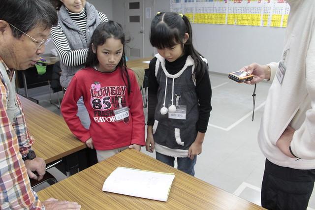 観察会開始前に,内藤先生にスケッチをみてもらう小学生.