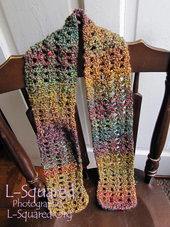 scarf with a square stitch design made with a fuzzy yarn in muted tones of gold, maroon and teal blue.