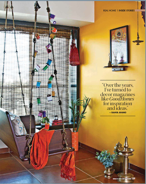 A modern apartment in Mumbai with traditional furniture, decor, and artifacts. A swing seen here against a mustard wall.