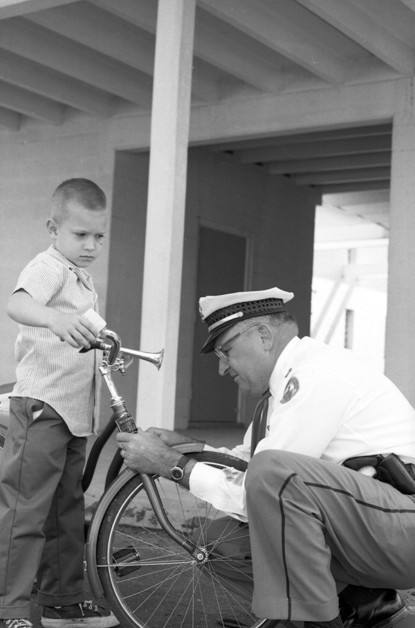 Sergeant Sid Keller inspecting Lloyd Mitchell's bicycle in Tallahassee, Florida