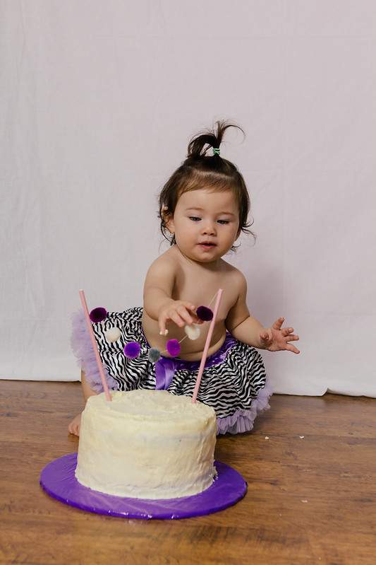 little girl in tutu with PomPom garland Smash cake