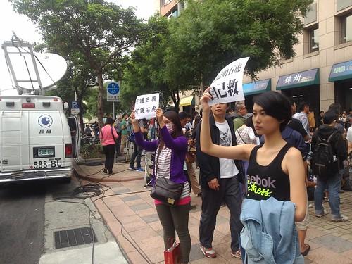 年輕人站在路邊舉標語,向路過的車輛展示訴求。攝影:詹嘉紋。
