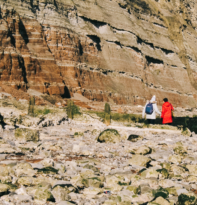 women walking alongside cliffs
