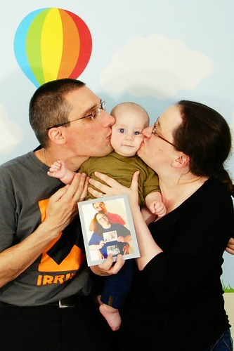 baby with daddy on one side and mummy on the other, both kissing his cheeks
