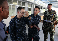 Hospital Corpsman 1st Class Justin Cayetano demonstrates how to label an injured person who has received a tourniquet on Hospital Corpsman 2nd Class Steven Nicholson as members of the Timor-Leste Defence Force look on. (U.S. Navy photo by Mass Communication Specialist 1st Class Bobby Northnagle)