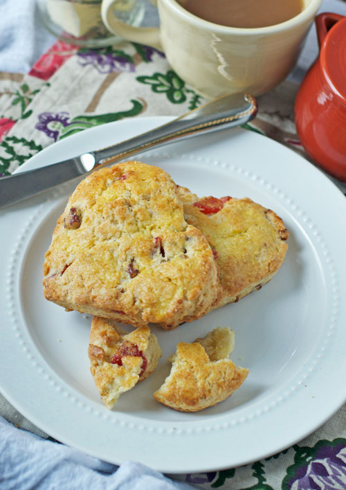 Two strawberry scones on a white plate in the shape of a heart