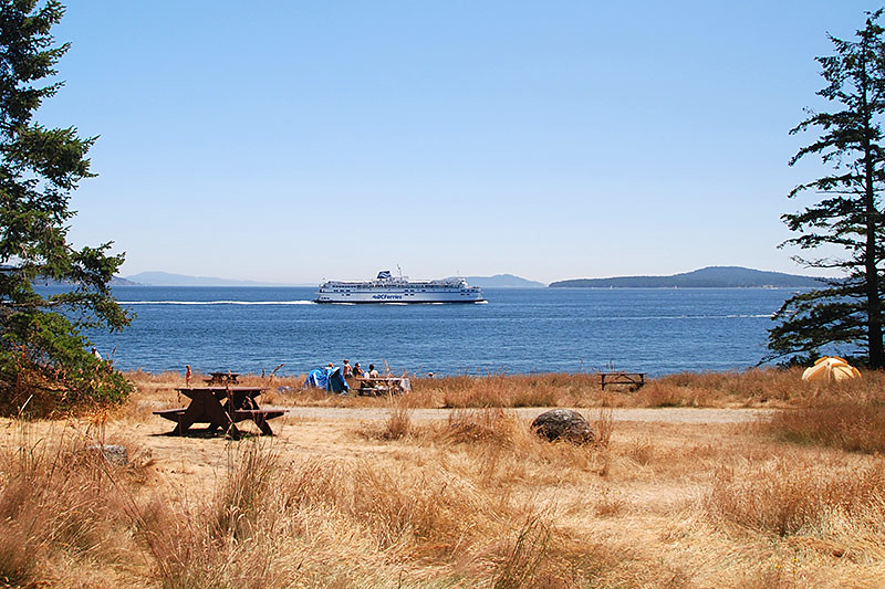 The Vancouver to Victoria BC Ferry passes campers at Ruckle Park, Saltspring Island, Gulf Islands National Park, British Columbia, Canada