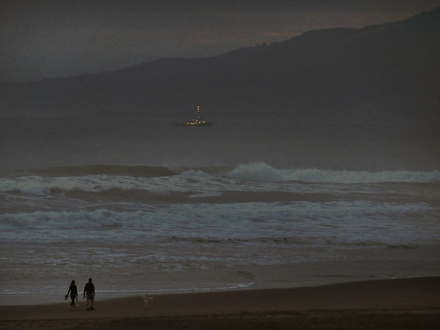 Couple walking their dog on Ocean Beach at dusk. San Francisco (2015)