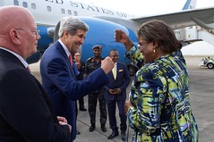 U.S. Secretary of State John Kerry fists bumps with Assistant Secretary of State for African Affairs Linda Thomas-Greenfield as she continues he travels on the Continent while he prepares to depart from the airport in Lagos, Nigeria, after he met with Nigerian President Goodluck Jonathan and his re-election challenger, retired Major-General Muhammadu Buhari, on January 25, 2015, for conversations urging both candidates to accept the results of their upcoming general-election vote. [State Department Photo/Public Domain]