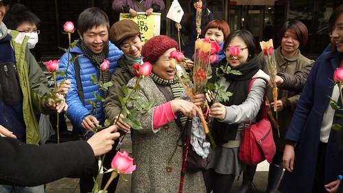 鄭燕收下民眾送的玫瑰花,笑容滿面