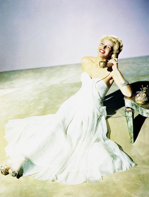 American actress Rita Hayworth (1918 - 1987) takes a phone call, circa 1948.