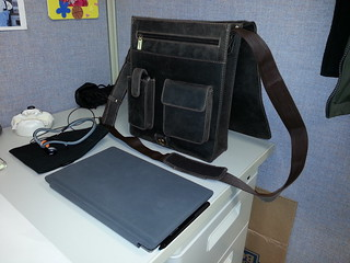 My Surface Pro 2 (closed it looks like a hardcover book) next to my man bag