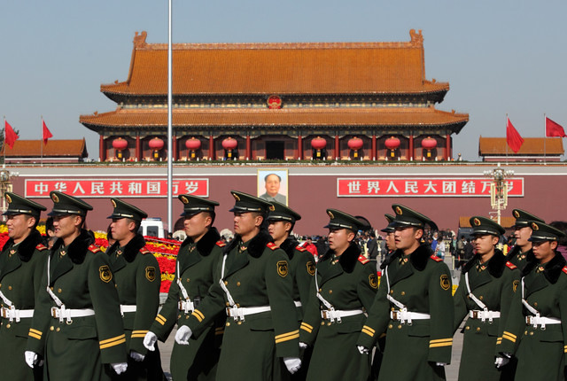 Members of China's People's Liberation Army (PLA) walk past the Tiananmen Gate in Beijing, China. Photographer: Tomohiro Ohsumi/Bloomberg