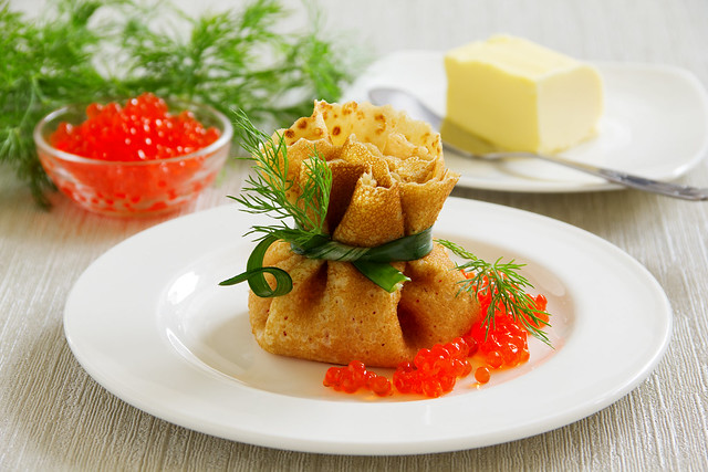 Traditional Russian pancakes with red caviar.