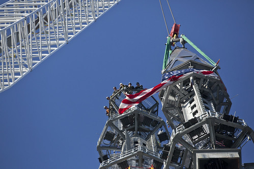 One World Trade Center spire rises to the top while workers away its arrival