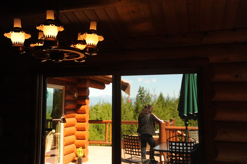 A neighbour standing on the deck taking in the view, wagon wheel lamp, patio furniture, through the sliding glass doors at Auntie's log cabin, Alderbrook Golf Course, Union, Washington, USA by Wonderlane