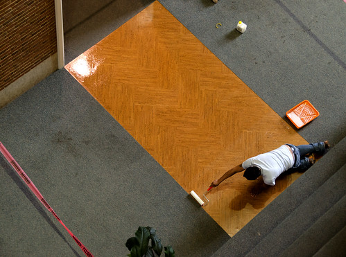 Worker Applying Sealant to Cork Floor Mockup