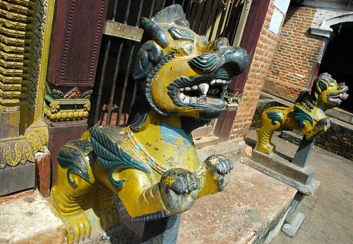 Symbols of protection, yellow and green lions protecting the Pamting Brothers Tibetan Buddhist and Nepalese shrine to Vajrayogini, Pharping, Nepal by Wonderlane