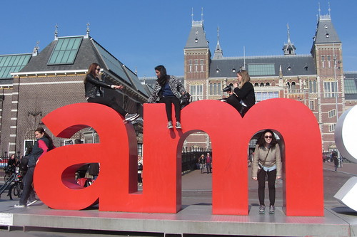 People pose on and around a large sculpture of the letters A and M