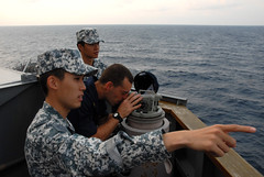 Republic of Singapore Navy Lt. Alvin Tan, bottom, points to an area in the South China Sea where a submarine periscope has been sighted by Ens. Matias del Castillo, center, during Cooperation Afloat Readiness and Training (CARAT) Singapore 2013. (U.S. Navy photo by Mass Communication Specialist 1st Class John Donohue)