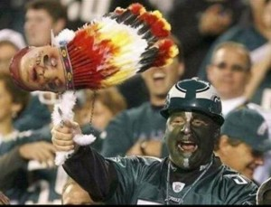 Fan holds costume severed Indian head.