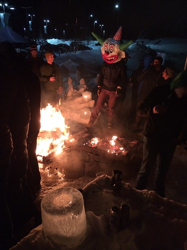 A person, wearing a costume clown head, standing behind a campfire at night, with other people around