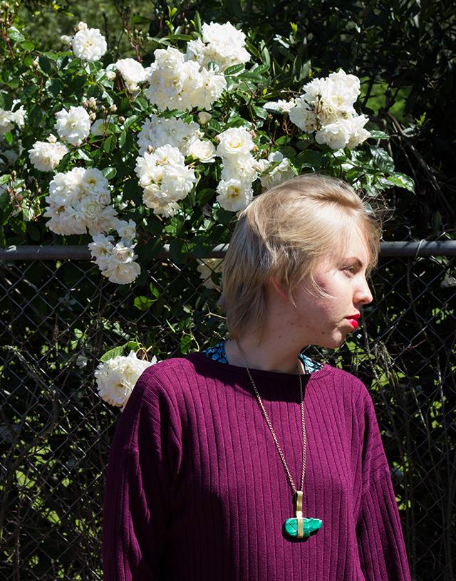 white roses, purple sweater, green bear pendant