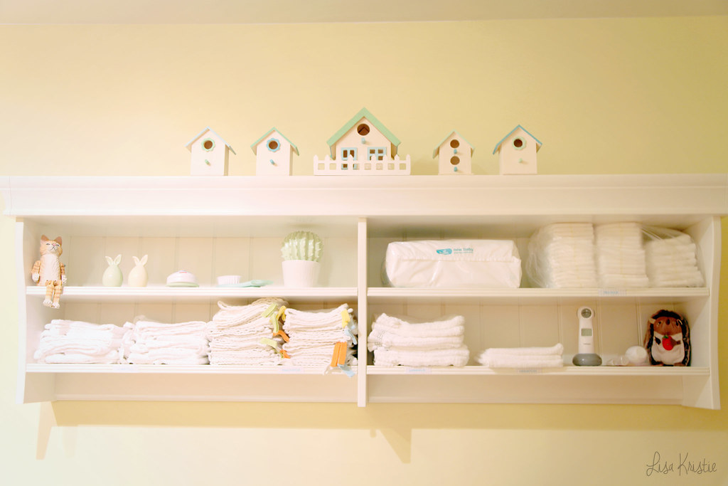 gender neutral baby nursery white ikea shelf bird houses organized diapers wash cloths organization care items thermometer