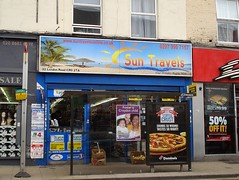 "A terraced shopfront with a sign above reading ""Sun Travels"" and the strapline ""Your Holiday Begins Here"".  The sign also shows a clear blue sky, sandy beach, and palm trees.  Some of the shopfront is obscured by a bus stop with two adverts on it, one reading ""Foster a Croydon child"" with a photo of three smiling people, and the other for Domino's pizza.  Lycamobile adverts are just visible on the shop itself."
