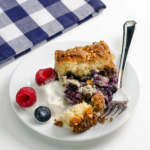 Blueberry Buckle on plate with fork, ice cream and berry garnish