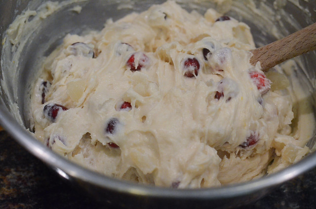A close up cake batter with cranberries and pear.
