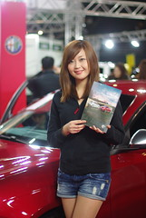 driving(0.0), automobile(1.0), exhibition(1.0), model(1.0), clothing(1.0), vehicle(1.0), girl(1.0), showgirl(1.0), auto show(1.0), lady(1.0), luxury vehicle(1.0),