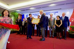 A Vietnamese official presents former U.S. Senator Bob Kerrey - Chairman of the Board of Trustees of the new Fulbright University Vietnam - is presented with the school's license during a ceremony attended by U.S. Secretary of State John Kerry on May 25, 2016, at the Rex Hotel in Ho Chi Minh City, Vietnam. [State Department photo/ Public Domain]
