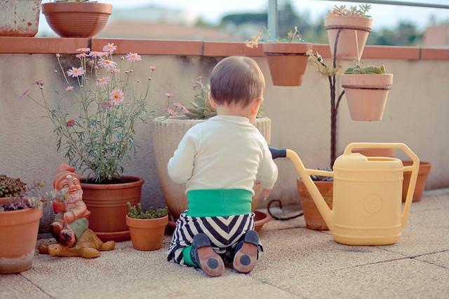 bébé sur terrasse arrosoir