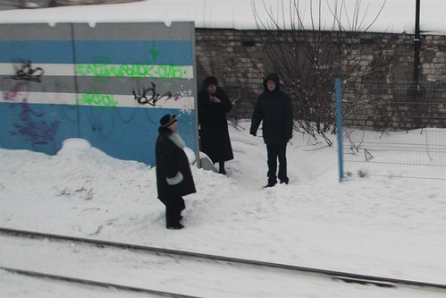 Locals beside a hole in the railway fence