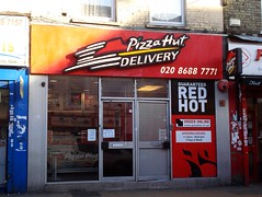"A small terraced shopfront with a large red sign above reading ""Pizza Hut Delivery"". There are two doors in the centre. To the left of the doors is a full-length window and to the right of the doors is a full-length panel reading ""Guaranteed Red Hot / Order online www.pizzahut.co.uk / Opening hours 11:30am-Midnight 7 Days A Week""."