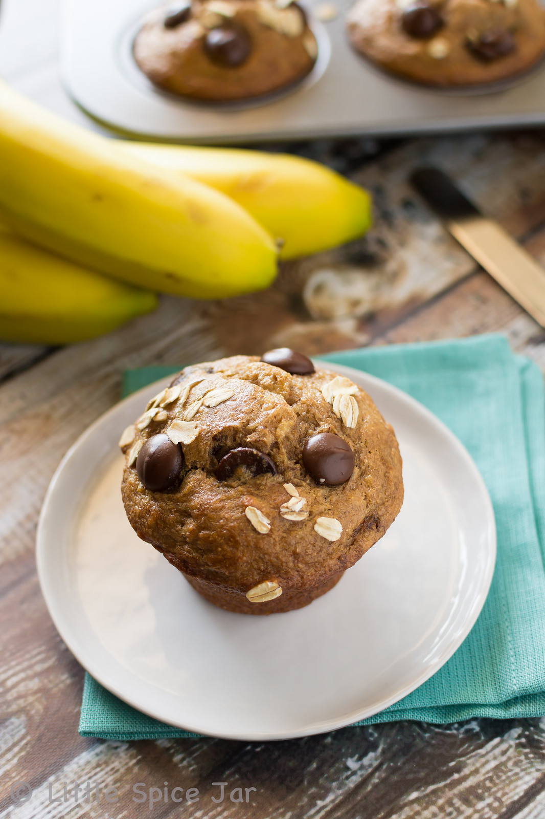 prepared muffin on white plate with bananas and more muffins in background