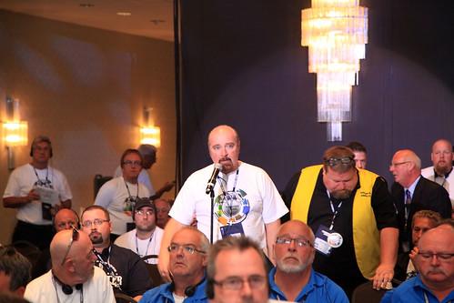 Male at Microphone Surrounded by Audience / Homme au micro entouré du public
