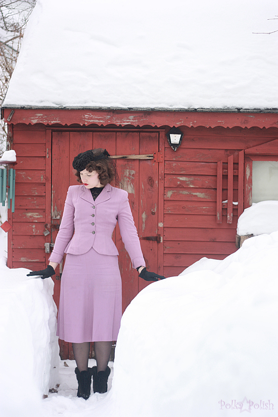 Light purple 1940s suit paired with fur overboots and a black tilt hat for winter